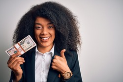 Young african american business woman with afro hair holding a bunch of cash dollars banknotes happy with big smile doing ok sign, thumb up with fingers, excellent sign