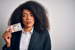 Young african american business woman with afro hair holding a bunch of cash dollars banknotes with a confident expression on smart face thinking serious
