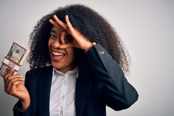 Young african american business woman with afro hair holding a bunch of cash dollars banknotes with happy face smiling doing ok sign with hand on eye looking through fingers