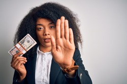 Young african american business woman with afro hair holding a bunch of cash dollars banknotes with open hand doing stop sign with serious and confident expression, defense gesture