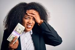 Young african american business woman with afro hair holding a bunch of 20 dollars banknotes stressed with hand on head, shocked with shame and surprise face, angry and frustrated. Fear and upset