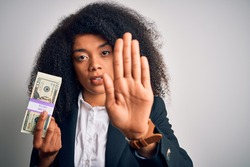 Young african american business woman with afro hair holding a bunch of 20 dollars banknotes with open hand doing stop sign with serious and confident expression, defense gesture