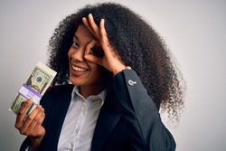 Young african american business woman with afro hair holding a bunch of 20 dollars banknotes with happy face smiling doing ok sign with hand on eye looking through fingers