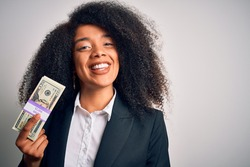 Young african american business woman with afro hair holding a bunch of 20 dollars banknotes with a happy face standing and smiling with a confident smile showing teeth