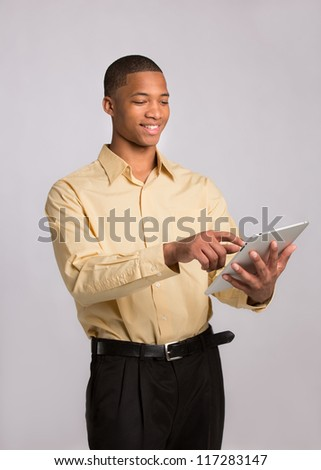 Young African American Businessman Texting on Tablet PC Pad on Grey Background