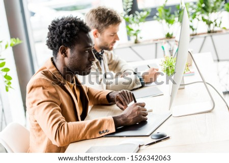young african american businessman using tablet and looking at computer monitor while sitting near colleague in office