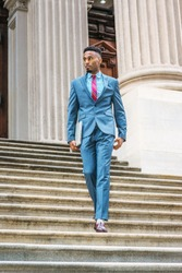 Young African American Businessman with beard working in New York, wearing sky blue suit, violet red patterned tie, dark purple leather shoes, holding laptop computer, walking down stairs from office.