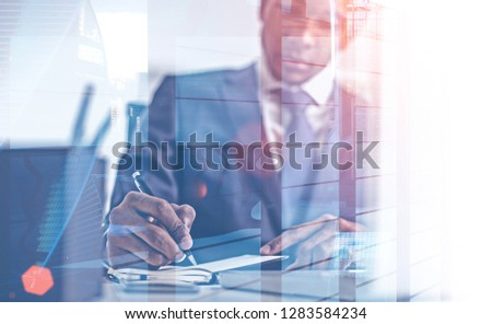 Young African American businessman writing in planner in his office with double exposure of skyscraper and cityscape. Toned image