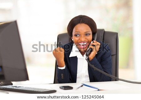 young african american businesswoman receiving exciting news in office