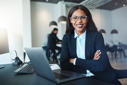 Young African American businesswoman smiling confidently while sitting with her arms crossed at her office desk with colleagues in the background