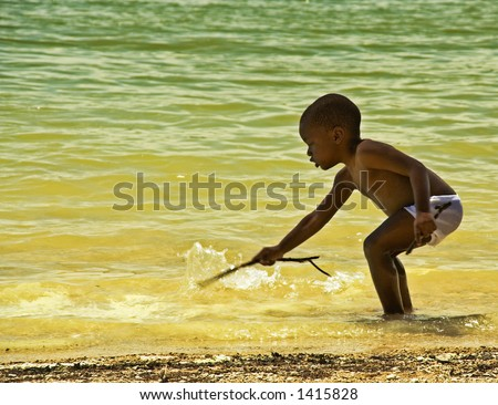 Young African American child playing with a stick in the water.