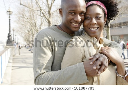 Young african american couple at London's river Thames, hugging and smiling.