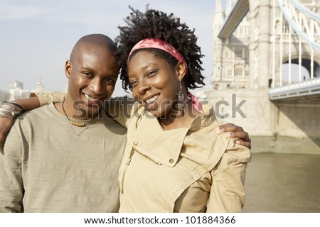 Young african american couple at London's Tower Bridge, hugging and smiling at camera.