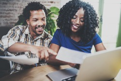Young African american couple checking bills together at the wooden table.Young black man and his girlfriend using laptop while working at home. Horizontal,blurred background.Cropped