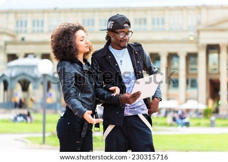 Young African American couple doing sightseeing with city map