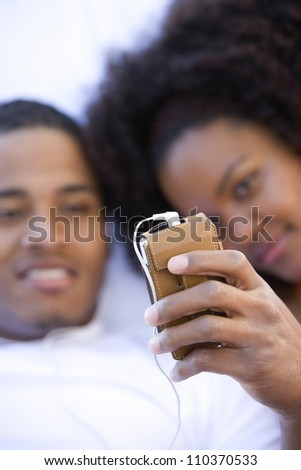 Young African American couple listening music through cell phone