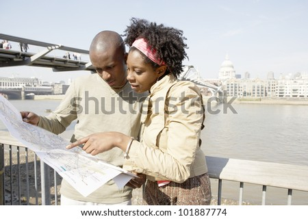 Young african american couple near London\'s St. Paul\'s Cathedral, looking at a map.