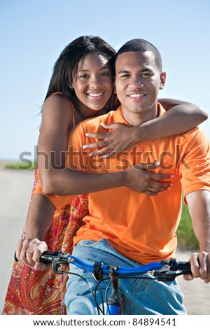 Young African American couple Outdoors Riding Bike Hug