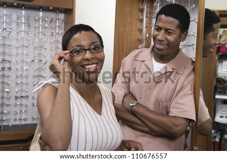 Young African American couple selecting eyeglasses at spectacles shop