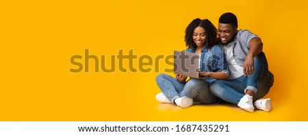 Young african american couple using laptop while sitting on floor over yellow background in studio, panorama with copy space