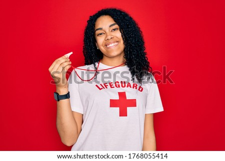 Young african american curly lifeguard woman wearing t-shirt with red cross using whistle with a happy face standing and smiling with a confident smile showing teeth Foto stock ©