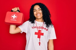 Young african american curly lifeguard woman wearing whistle holding first aid kit with a happy face standing and smiling with a confident smile showing teeth