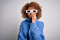 Young african american curly woman wearing 3d glasses over isolated white background looking stressed and nervous with hands on mouth biting nails. Anxiety problem.