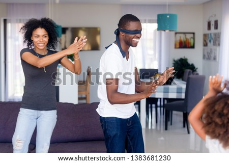 Young African American dad with eyes blindfolded play hide and seek with wife and daughter, black happy family have fun together, entertaining engaged in funny games, spend time at home