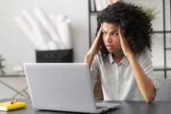 Young African American female office worker feeling stressed, annoyed from the office noise, looking away, touching temples, suffering from severe headache migraine, overwhelmed with computer works