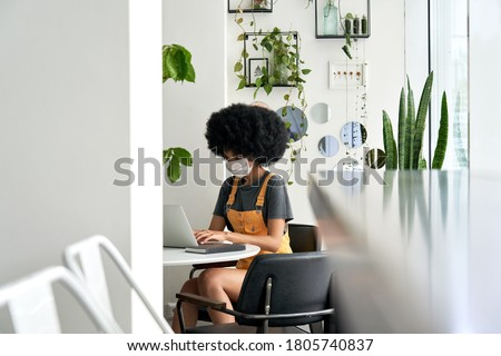 Young African American female student with Afro hair wearing face mask using laptop sitting at cozy cafe table alone indoor. Social distancing and work, study on computer with covid 19 protection.