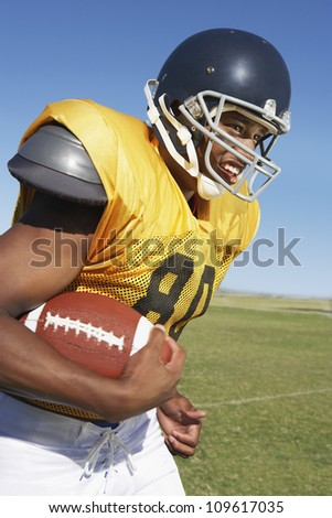 Young African American football player runs while holding ball