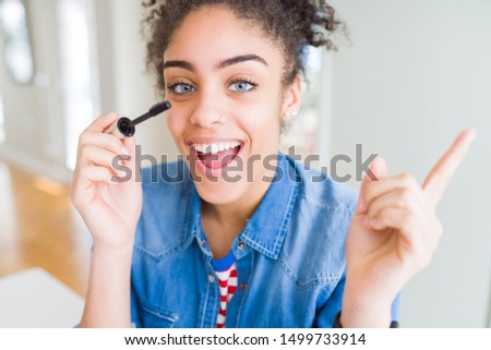 Young african american girl applying eyelashes mascara very happy pointing with hand and finger to the side