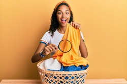 Young african american girl holding magnifying glass looking for stain at clothes celebrating crazy and amazed for success with open eyes screaming excited.
