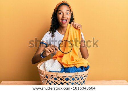Photo of  Young african american girl holding magnifying glass looking for stain at clothes celebrating crazy and amazed for success with open eyes screaming excited.