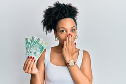 Young african american girl holding 100 polish zloty banknotes covering mouth with hand, shocked and afraid for mistake. surprised expression