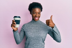 Young african american girl holding take away coffee smiling happy and positive, thumb up doing excellent and approval sign