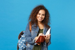 Young african american girl teen student in denim clothes, backpack hold books isolated on blue background studio portrait. Education in high school university college concept. Mock up copy space