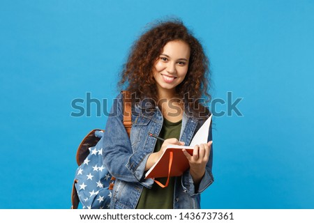 Young african american girl teen student in denim clothes, backpack hold books isolated on blue background studio portrait. Education in high school university college concept. Mock up copy space Foto stock ©