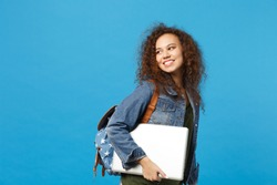 Young african american girl teen student in denim clothes, backpack hold pc isolated on blue wall background studio portrait. Education in high school university college concept. Mock up copy space