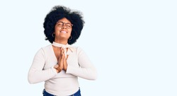 Young african american girl wearing casual clothes and glasses begging and praying with hands together with hope expression on face very emotional and worried. begging.