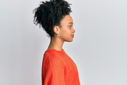 Young african american girl wearing casual clothes looking to side, relax profile pose with natural face and confident smile.