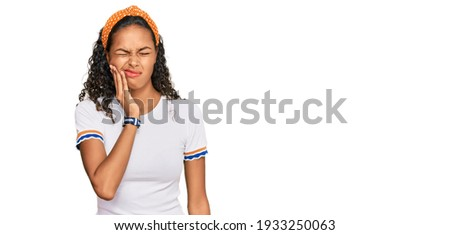 Young african american girl wearing casual clothes touching mouth with hand with painful expression because of toothache or dental illness on teeth. dentist  Сток-фото ©
