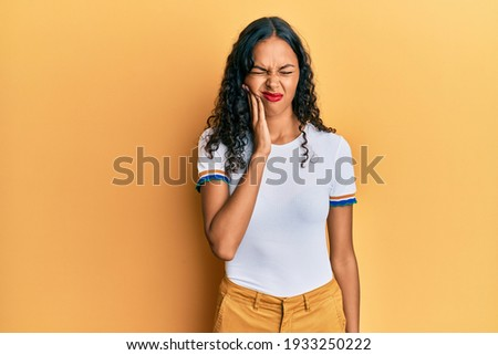 Young african american girl wearing casual clothes touching mouth with hand with painful expression because of toothache or dental illness on teeth. dentist  Stock photo ©