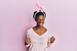 Young african american girl wearing cute easter bunny ears excited for success with arms raised and eyes closed celebrating victory smiling. winner concept.