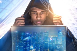Young African American hacker in a black hoodie looking at his laptop screen. Double exposure of a night city. Morning cityscape background. Toned image