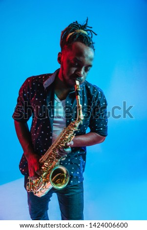 Young african-american jazz musician playing the saxophone on blue studio background in trendy neon light. Concept of music, hobby. Joyful attractive guy improvising. Retro colorful portrait of artist Сток-фото ©