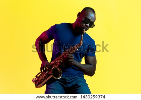 Young african-american jazz musician playing the saxophone on yellow studio background in trendy neon light. Concept of music, hobby. Joyful attractive guy improvising. Colorful portrait of artist. #1430259374