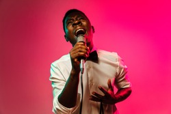 Young african-american jazz musician singing a song on gradient pink-red background in neon light. Concept of music, hobby, festival, open-air. Joyful guy improvising. Colorful retro portrait of