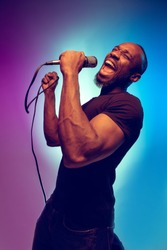 Young african-american jazz musician singing a song on gradient purple-blue background. Concept of music, hobby. Joyful attractive guy improvising, having a concert. Colorful retro portrait of singer.