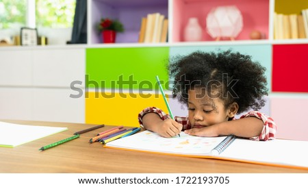 Young African American kid girl drawing with colored pencil, preschool child study at home school. Children education, self isolation, coronavirus outbreak social distancing or homeschooling concept